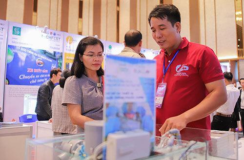 Anh Đào Phước Xoàn (áo đỏ) giới thiệu cho khách tham quan về cách vận hành hệ thống nuôi tôm thông minh. Ảnh: Nguyễn Đông.